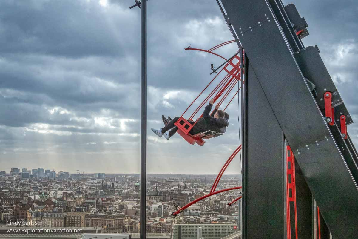 two men swinging far above a city