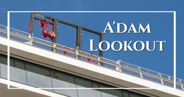 """view up to people in a swing on a rooftop with text """"A'DAM LOOKOUT"""""""