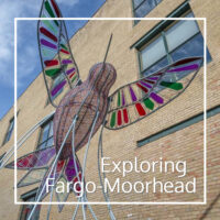 "metal hummingbird sculpture with text ""Exploring Fargo-Moorhead"""
