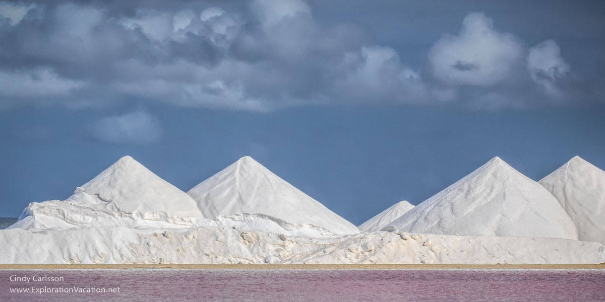 large piles of salt above pink water