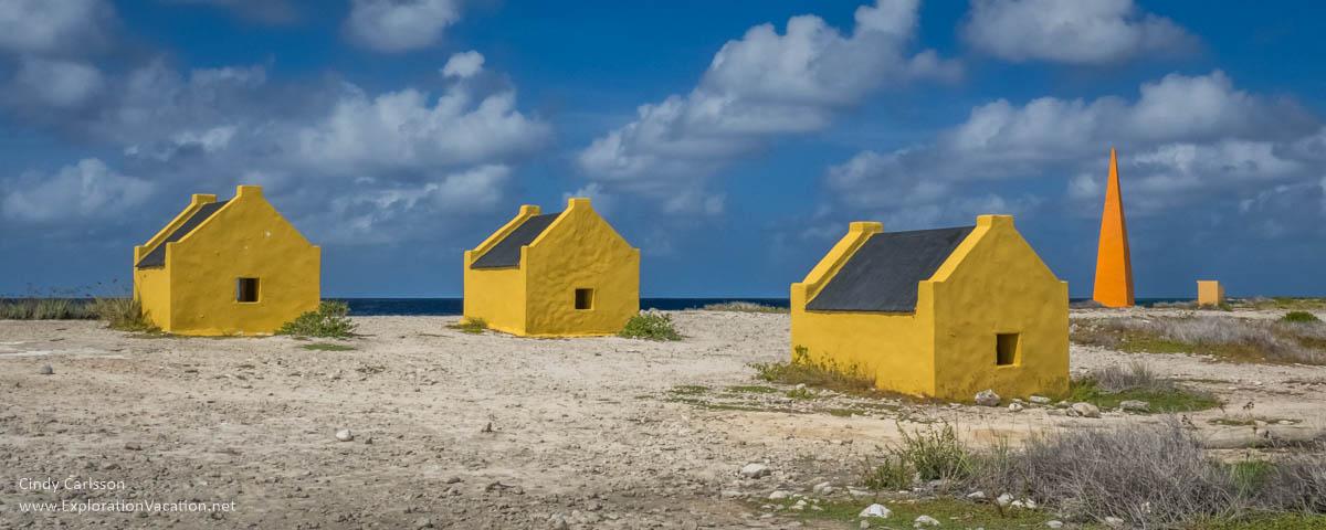 small yellow huts along the sea