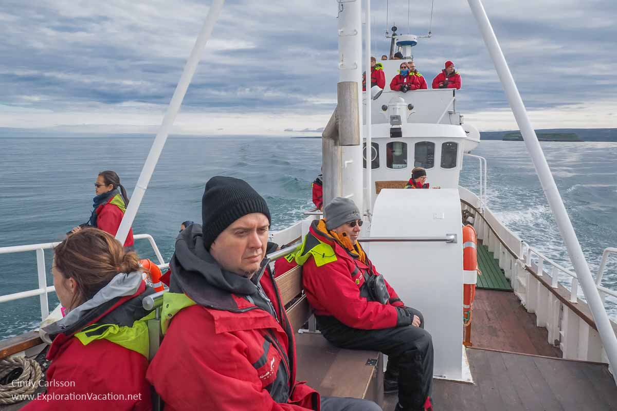 passengers in foul weather gear on a boat