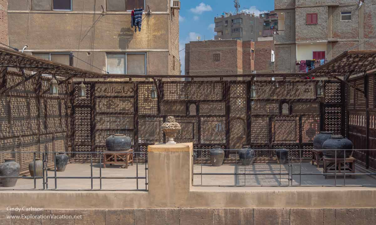 wood lattice and storage jars on a rooftop terrace in Cairo