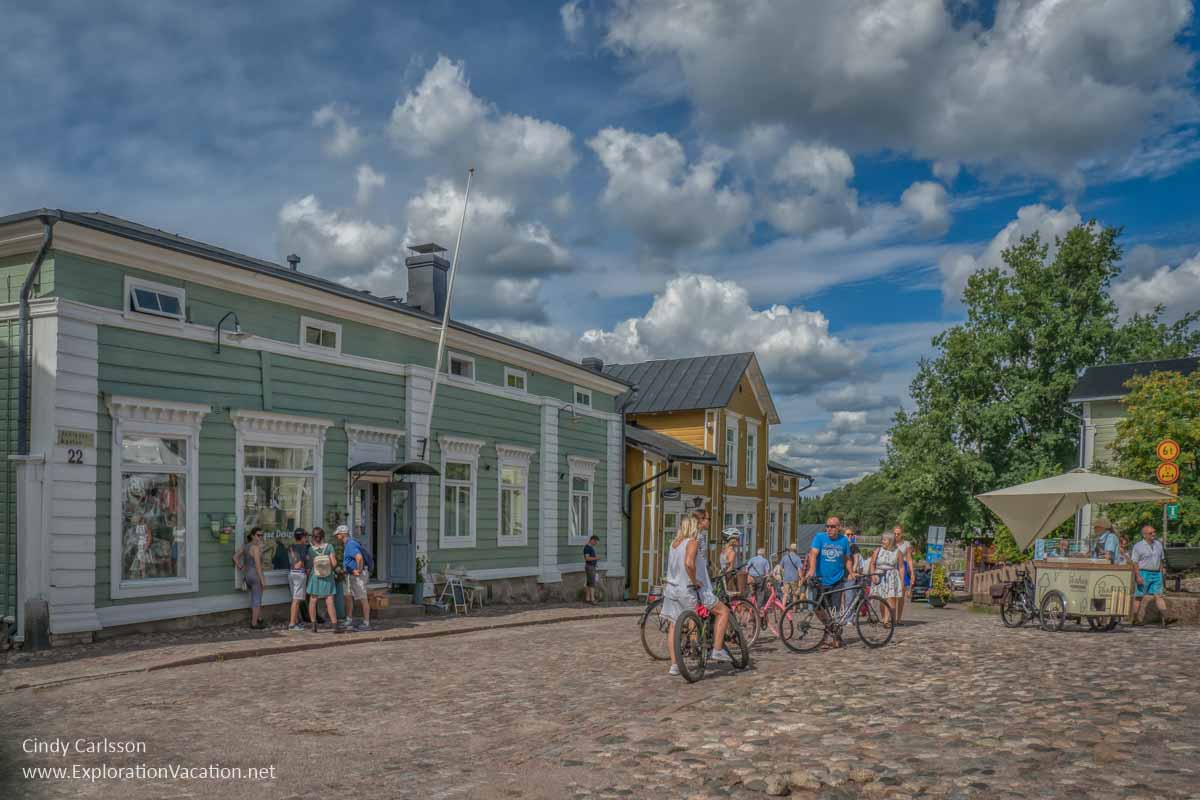 people in a square with historic wooden buildings in Finland