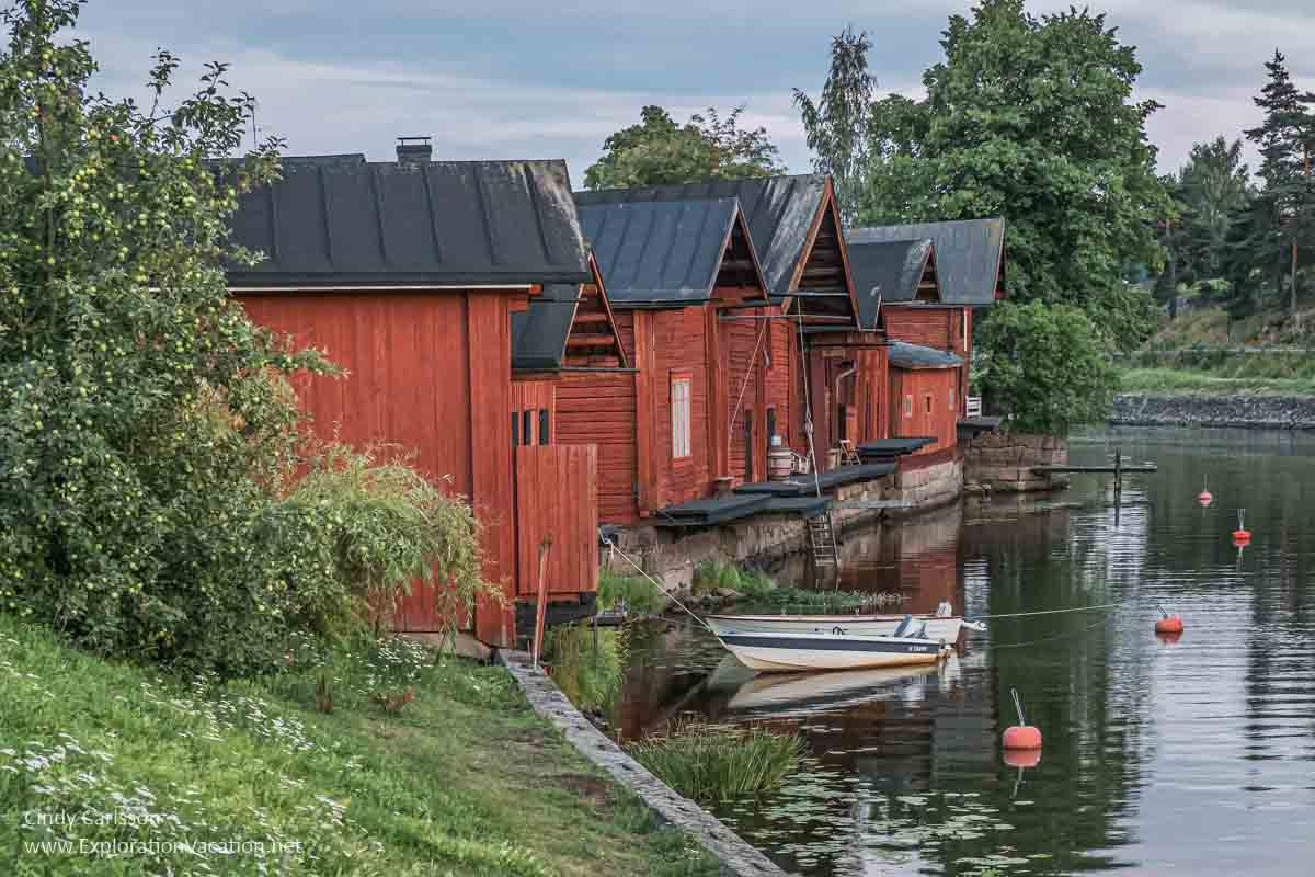 red Nordic buildings along a river in Finland