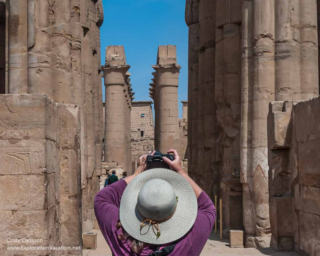 photo of a woman with a big hat taking a picture of the pillars of Karnak Temple in Egypt