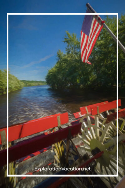 paddlewheel on a boat with river and USA flag