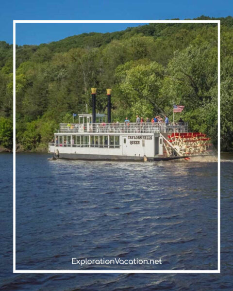 paddlewheel boat on a river by a forested hillside