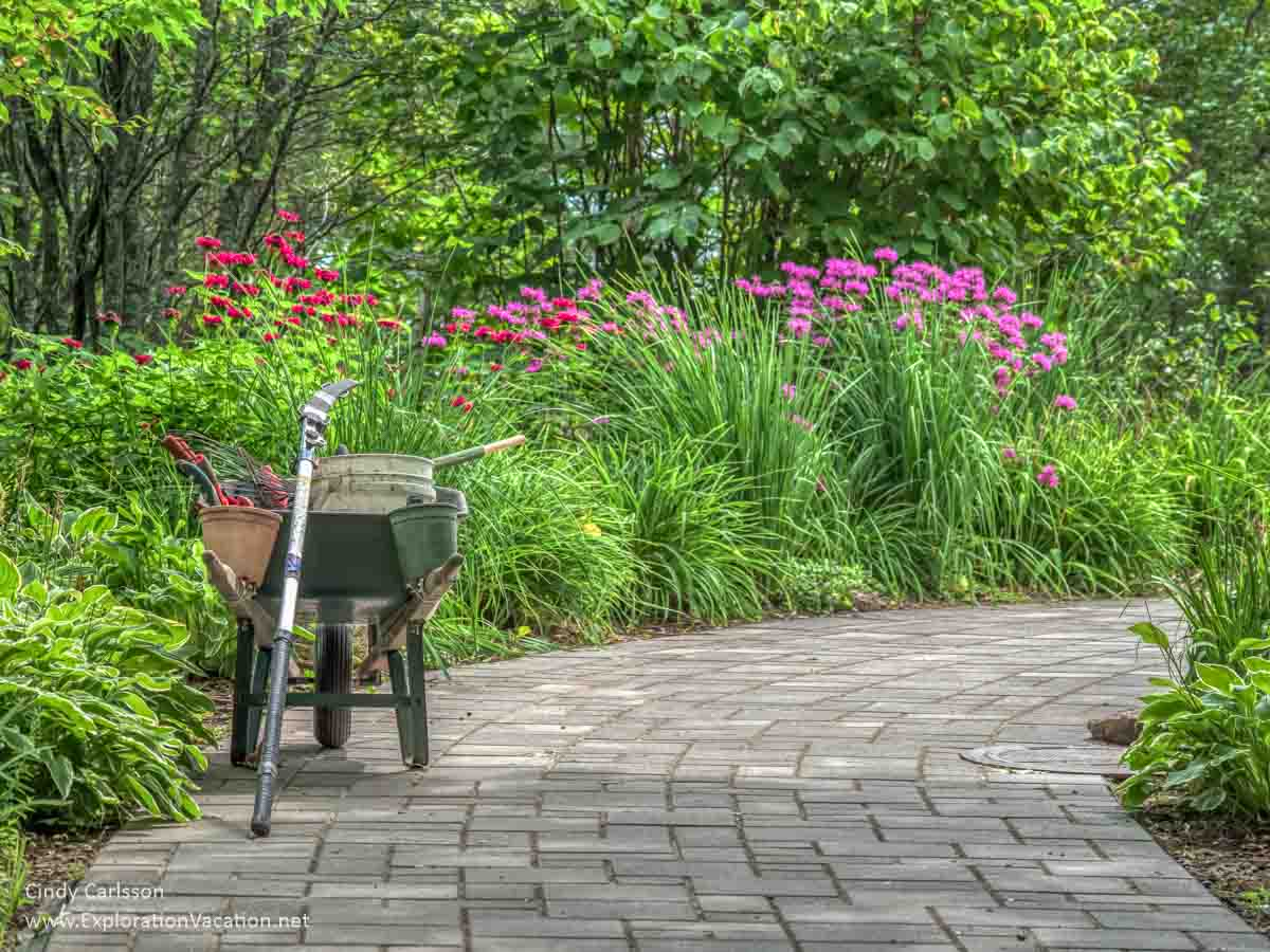 formal pathway with flowers and wheelbarrow with gardening tools