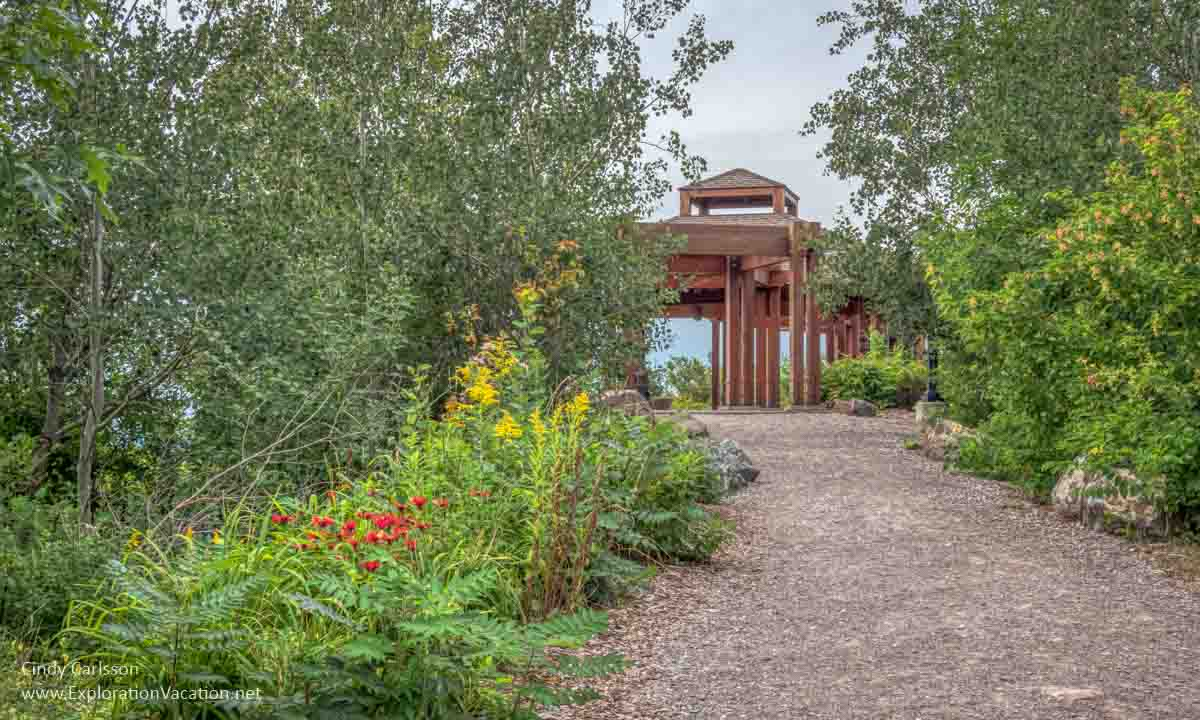 flower-lined path leading to a large gazebo