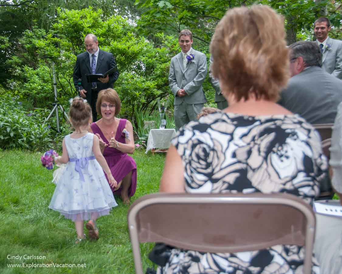 flower girl, wedding party, and a woman's back at a wedding in Duluth's Enger Park