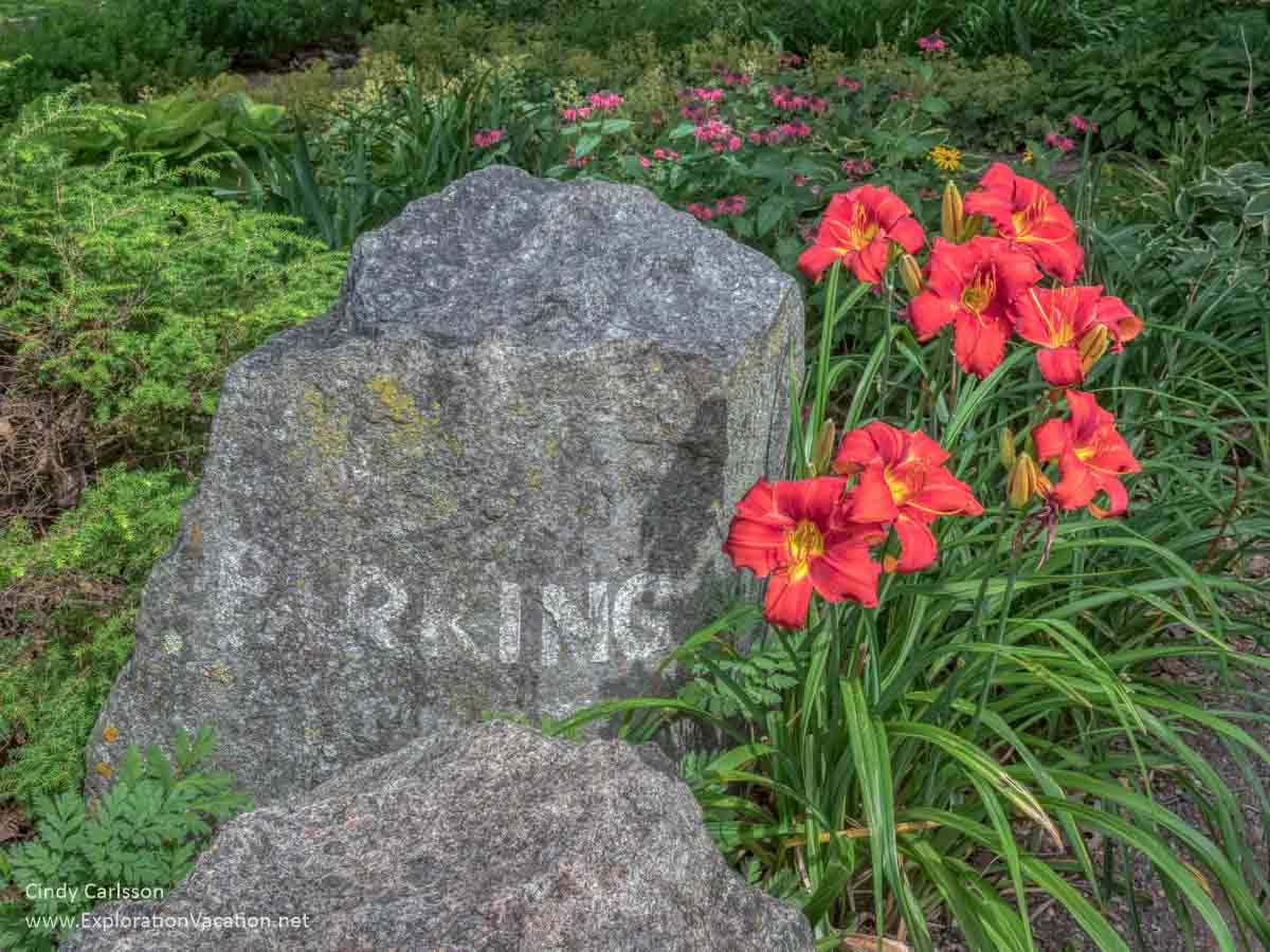 """stone that has """"parking"""" carved on it with red/orange day lilies"""