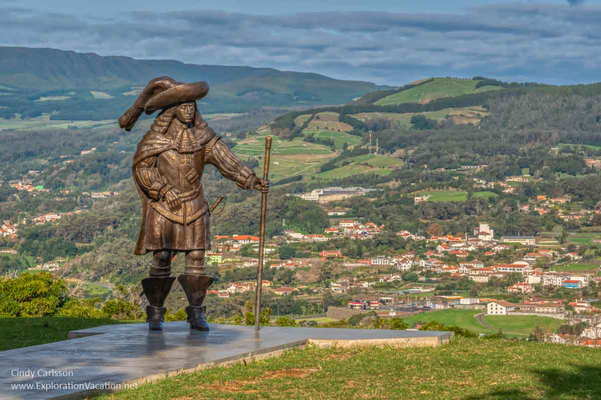 life-size bronze statue of a Portuguese leader with views of a city and green hills in the background