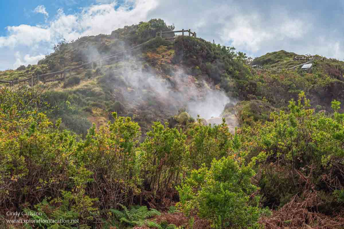 green hillside with steam rising from geothermal activity on Terceira Azores