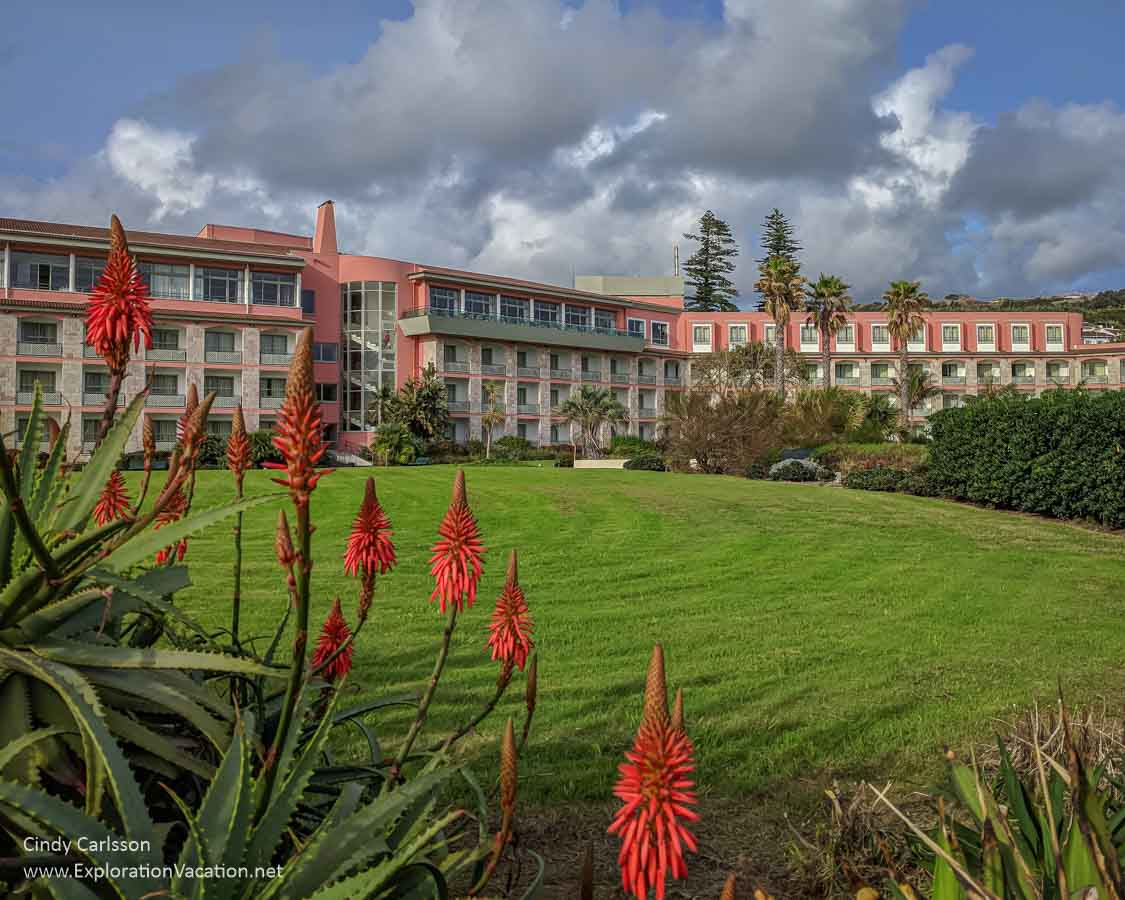 a brightly colored hotel with lawn and large aloes